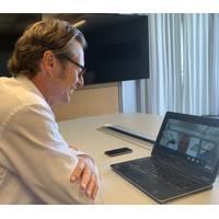 DNV GL - Maritime CEO Knut Ørbeck-Nilssen (left), speaks with Juha Koskela, Managing Director, ABB Marine & Ports, via laptop at the signing. (Photo: DNV GL)