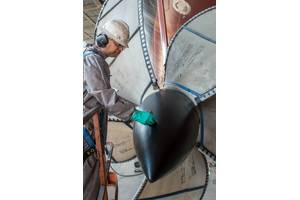 Lindell Toombs, a Newport News shipbuilder with 41 years of experience, applies a protective coating to one of the four propellers on the aircraft carrier Gerald R. Ford (CVN 78). Photo by Chris Oxley