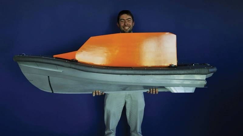 Naval architect Peter Eyre with his model of the Shannon lifeboat's hull. (Photo: RNLI/Nigel Millard)